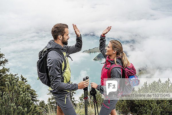 Happy young couple on a hiking trip in the mountains high fiving  Herzogstand  Bavaria  Germany