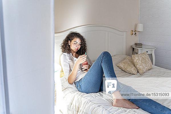 Entspannte junge Frau liegt mit gesundem Getränk im Bett