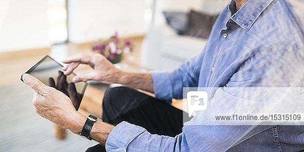 Nahaufnahme eines älteren Mannes mit Tablette zu Hause