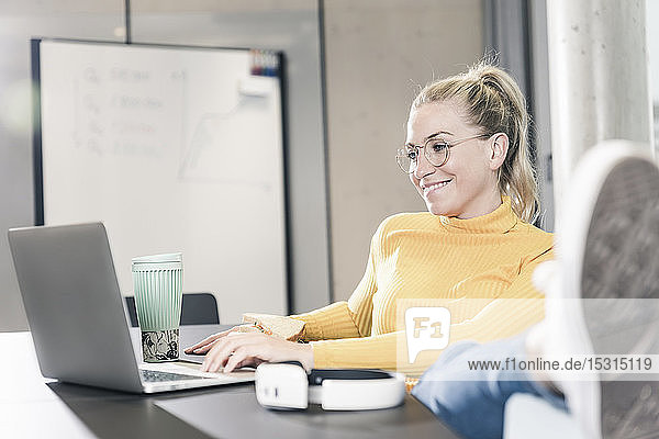 Smiling casual businesswoman sitting at table in office using laptop and eating a sandwich