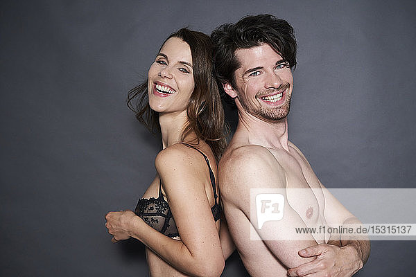 Portrait of happy semi-dressed couple back to back