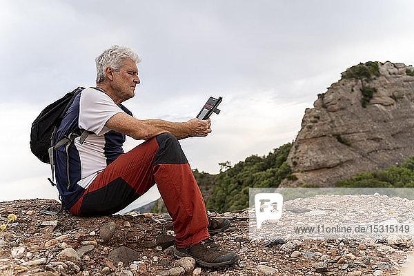 Senioren-Wanderer mit Smartphone,  auf dem Aussichtspunkt sitzend