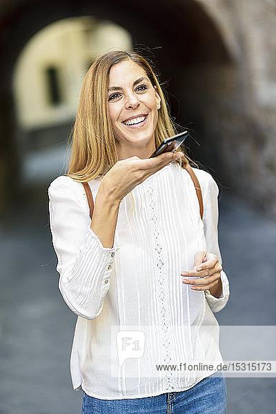 Glückliche Frau mit Smartphone in der Stadt