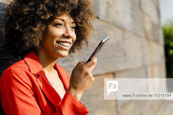 Porträt einer lächelnden jungen Frau am Telefon in modischer roter Anzugsjacke