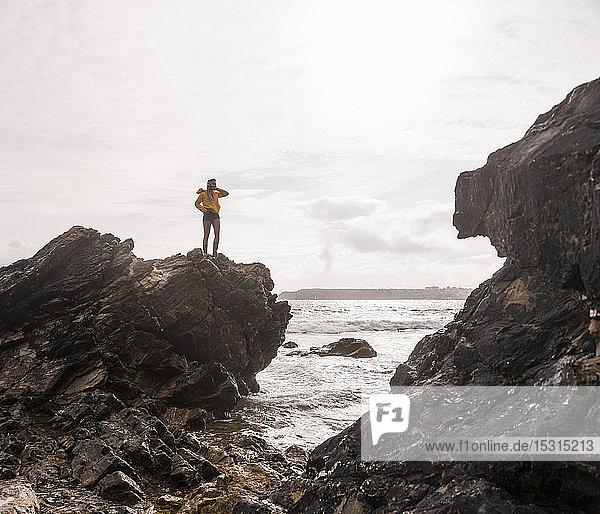 Frau in gelber Regenjacke auf Felsen stehend
