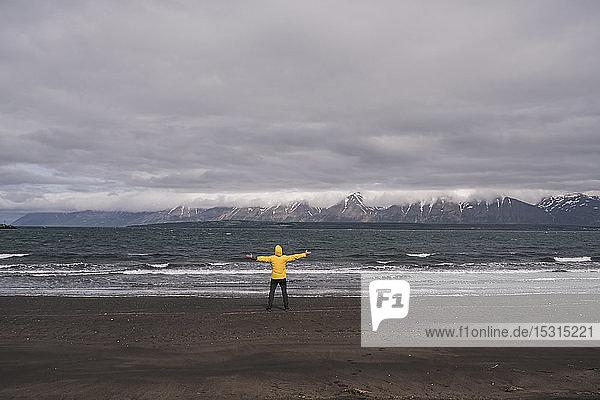 Matuer Mann steht mit ausgestreckten Armen am Lavastrand des Eyjafjordurfjord  Island