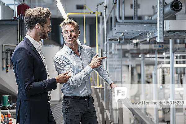Two businessmen talking in a modern factory