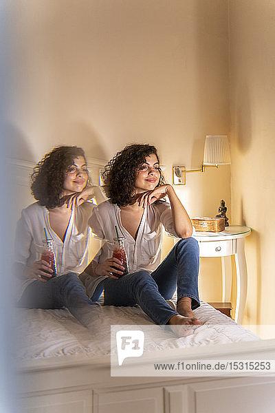 Entspannte junge Frau sitzt mit gesundem Getränk im Bett