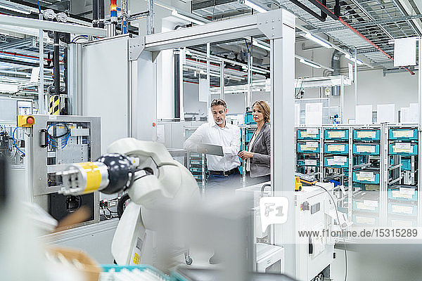 Businesswoman and manwith tablet talking in a modern factory