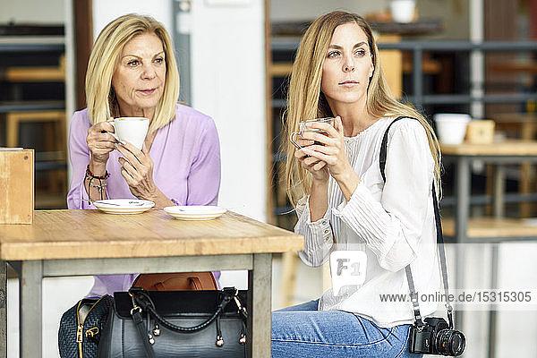Reife Frau mit ihrer Tochter  die Kaffee und Tee trinkt und an einem Tisch im Freien in einem Café sitzt