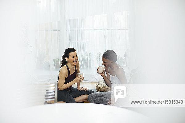 Zwei glückliche Frauen sitzen auf einer Gymnastikmatte und trinken zu Hause Tee