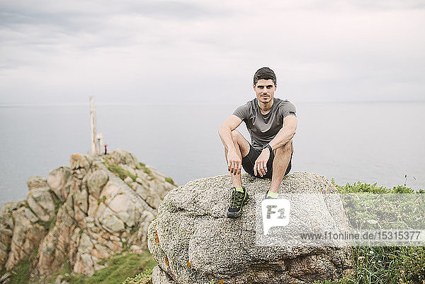 Porträt eines Trailrunners  der auf einem Felsen in der Küstenlandschaft sitzt  Ferrol  Spanien