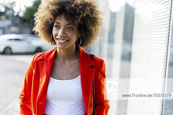 Porträt einer lächelnden jungen Frau in modischer roter Anzugsjacke