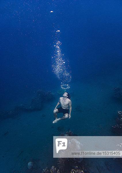 Junger Mann taucht unter Wasser