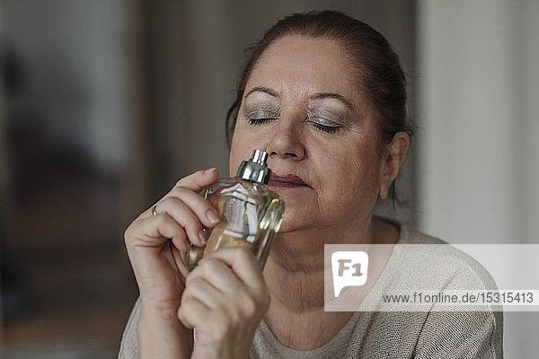 Ältere Frau riecht an Parfümflakon