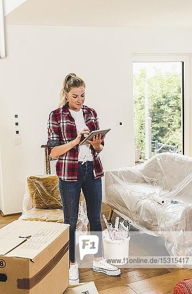 Frau zieht mit Tablette in neues Zuhause ein