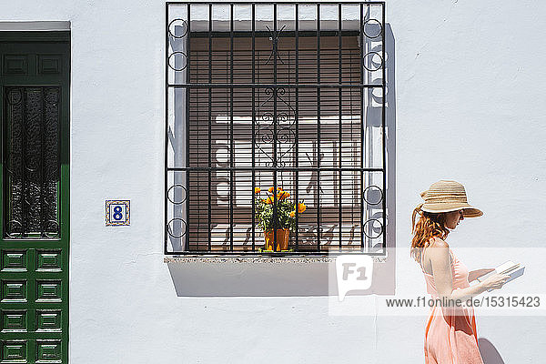 Redheaded young woman reading a book in front of a house  Frigiliana  Malaga  Spain
