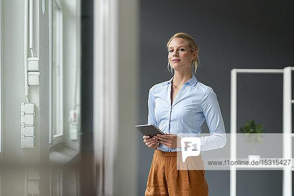 Porträt einer jungen Geschäftsfrau mit Tablett im Büro