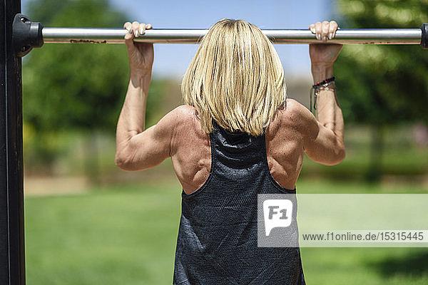 Rückansicht einer reifen Frau  die an einer Bar in einem Park trainiert