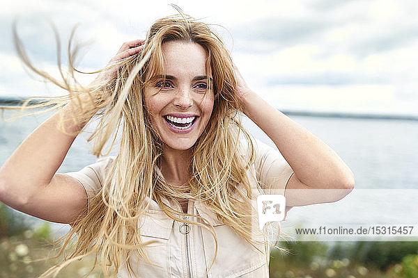 Porträt einer lachenden Frau am Seeufer