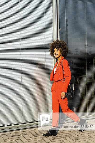 Lächelnde junge Frau mit Umhängetasche in modischem roten Hosenanzug