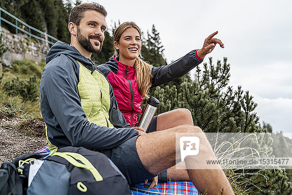 Happy young couple on a hiking trip in the mountains having a break  Herzogstand  Bavaria  Germany