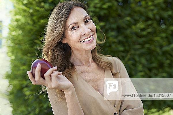Bildnis einer reifen Frau  die einen Apfel hält  im Hintergrund eine Hecke