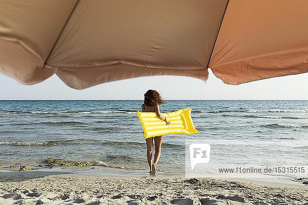 Junge Frau mit gelbem Luftbett am Strand