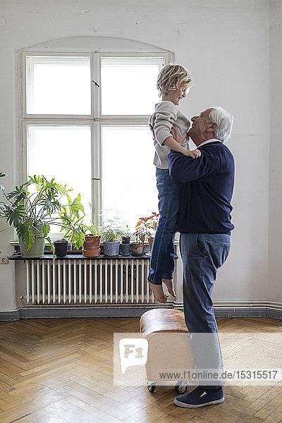 Großvater hebt Enkel zu Hause hoch