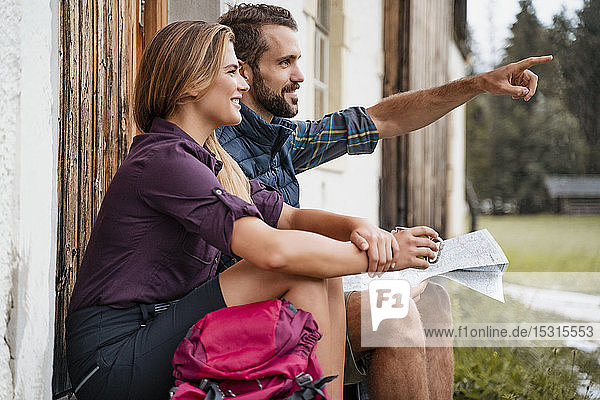 Young couple with map at a farmhouse during a hiking trip  Vorderriss  Bavaria  Germany