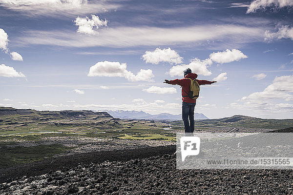 Hiker in Vesturland  Iceland  standing with arms out and looking at landscape