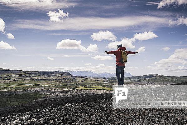 Wanderer in Vesturland  Island  steht mit ausgestreckten Armen da und schaut in die Landschaft
