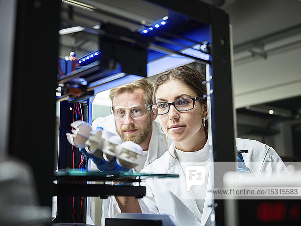 Two technicians looking at turbine wheel being printed in 3d printer