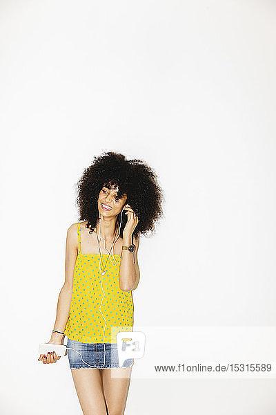 Junge Frau benutzt ihr Mobiltelefon zum Musikhören  weißer Hintergrund