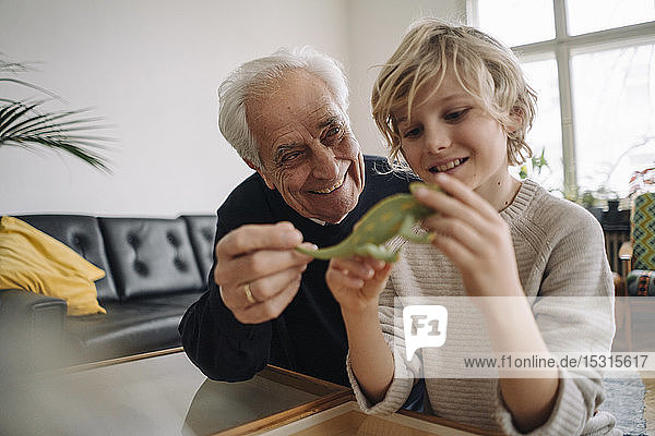 Glücklicher Großvater und Enkel spielen zu Hause mit Spielzeug-Chamäleon