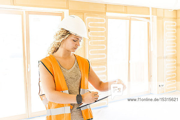 Young woman checking the construction of a new wooden house