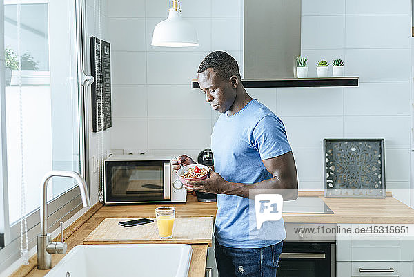 Young man having breakfast in kitchen at home