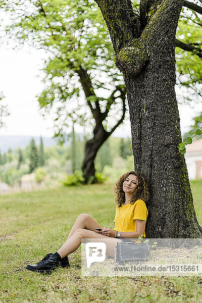 Portrait of smiling young woman sitting in a park