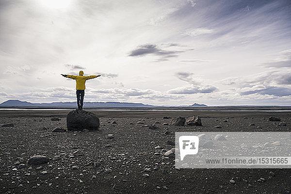 Erwachsener Mann steht mit ausgestreckten Armen auf einem Felsen im vulkanischen Hochland von Island