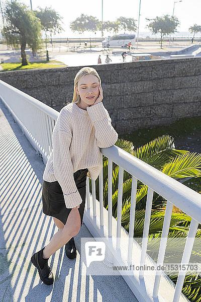 Porträt einer blonden jungen Frau  die auf einem Steg steht und sich entspannt