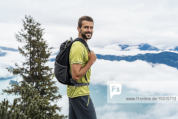 Portrait of smiling young man on a hiking trip in the mountains  Herzogstand  Bavaria  Germany