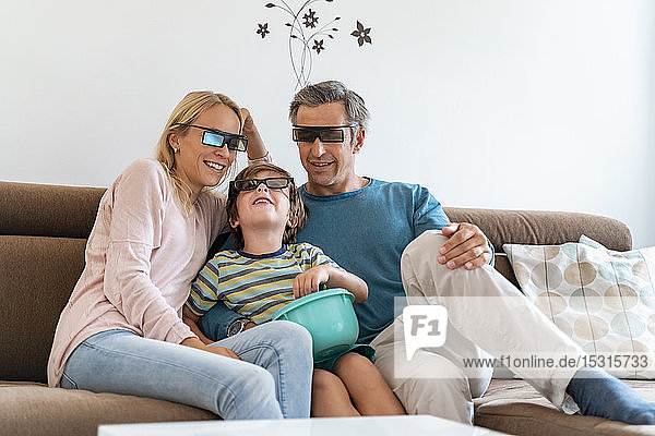 Father  mother and son wearing 3d glasses on couch at home watching Tv