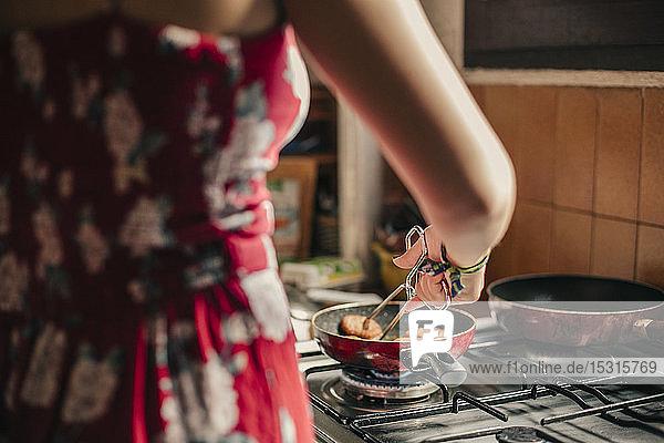 Nahaufnahme einer Frau  die in der Küche mit einer Pfanne kocht