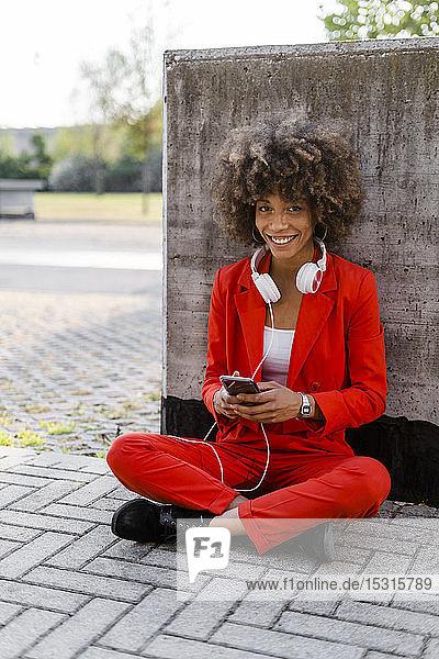 Porträt einer lächelnden jungen Frau mit Smartphone und Kopfhörer im modischen roten Hosenanzug