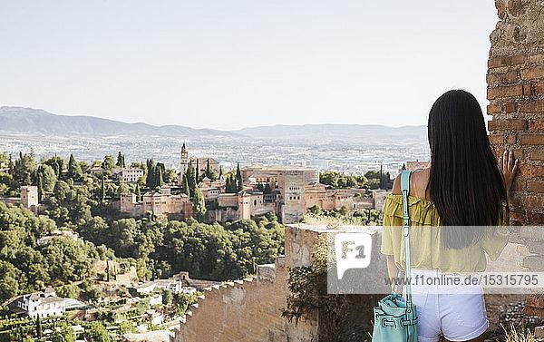 Rückansicht einer jungen Frau mit Blick auf die Alhambra  Granada  Spanien