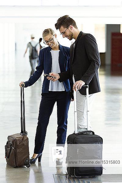 Zwei lächelnde junge Geschäftspartner mit einem Smartphone am Flughafen