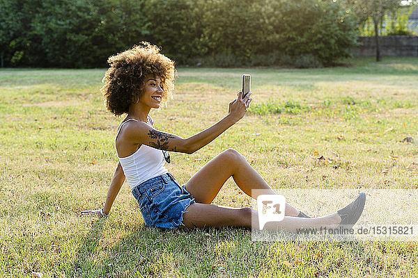 Tätowierte junge Frau  die auf einer Wiese sitzt und sich mit ihrem Smartphone selbstständig macht