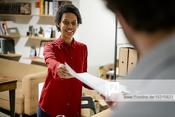 Businesswoman handing over paper to colleague in office