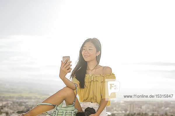 Smiling young woman taking a selfie above Granada  Spain