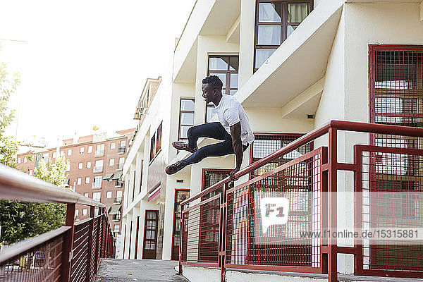 Young man jumping across a fence in the city